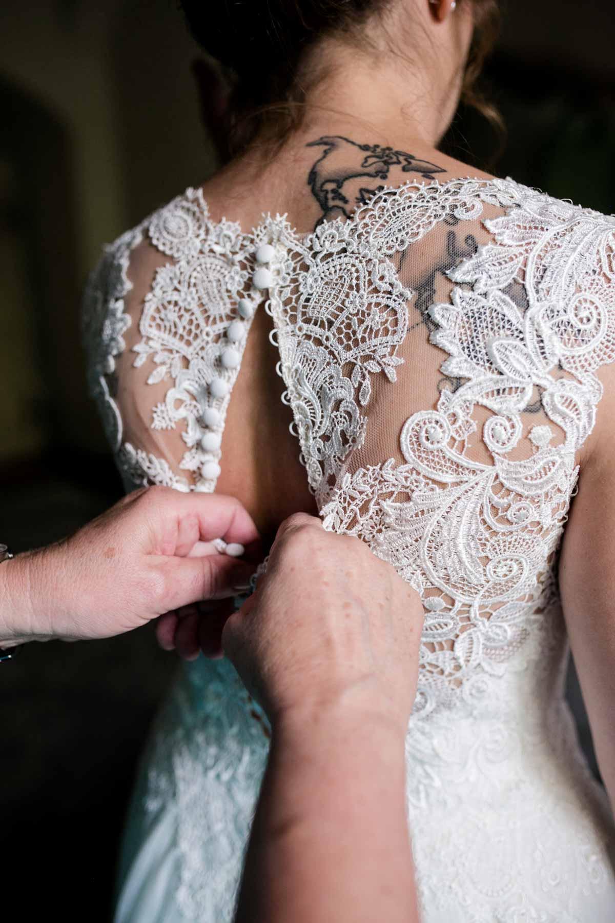 Braut schlüpft in ihr Brautkleid