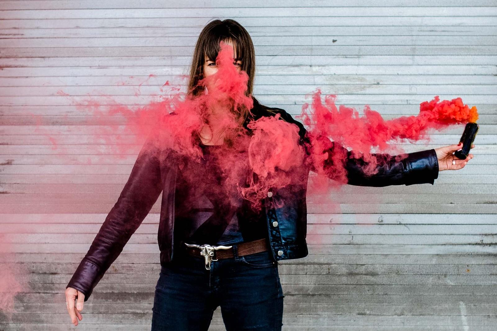 Portraitfoto einer Frau mit roter Rauchbombe