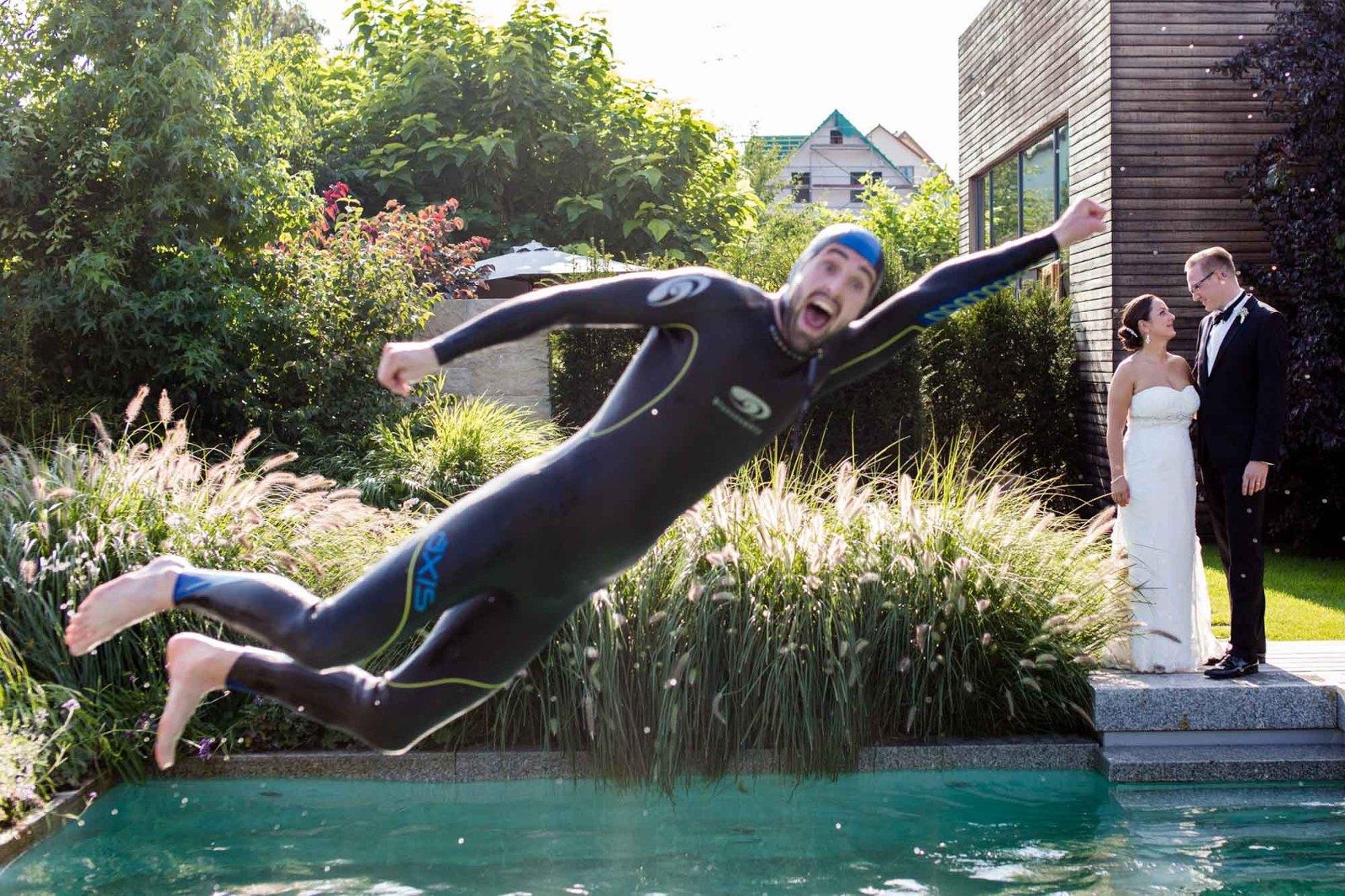 Taucher springt in einen Pool mit Hochzeitspaar im Hintergrund